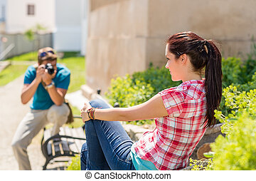 Young man take photo of his girlfriend sitting park bench