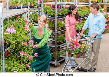 Garden center worker pushing flower shelves customers...