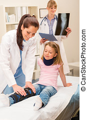 Pediatrician examining girl broken leg - Two female doctors...