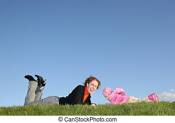 mother with baby lies on grass