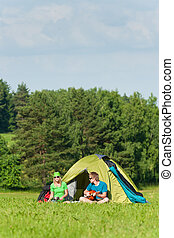 Young camping couple cooking meal play guitar
