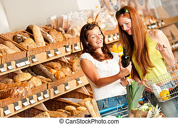 Grocery store: Two women choosing wine in a supermarket