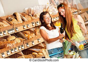 Grocery store: Two women choosing wine in a supermarket
