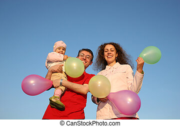 family with baby and balloons
