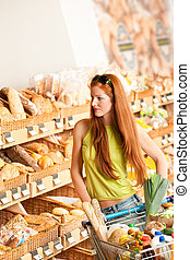 Grocery store: Red hair woman with shopping cart at bakery