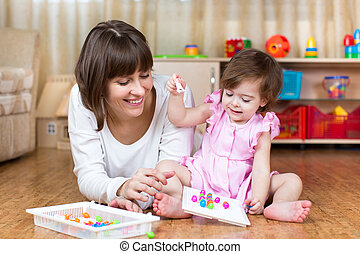 mother and kid play together in home interior