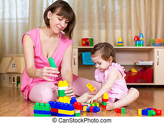 mother and her kid play with block toys at home interior