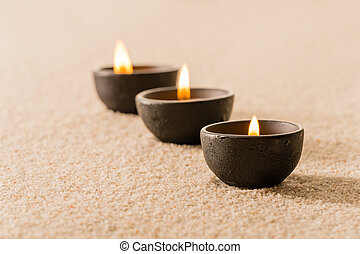 Spa therapy three candles on sand