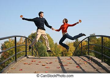 jump couple on autumn bridge