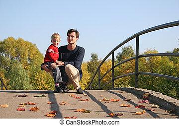 father with son on autumn bridge