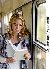 Woman reading book on train hall vacation
