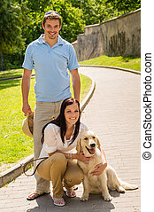 Happy couple with dog on park alley - Happy young couple...