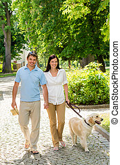 Young couple in love walking dog park - Couple in love...