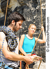 Rock climbing man showing woman rope knot - Rock climbing...