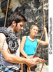 Rock climbing man showing woman rope knot - Rock climbing...