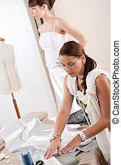 Fashion model fitting white wedding dress by designer -...