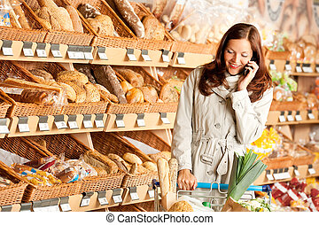 Grocery store: Young brown hair woman with mobile phone and...