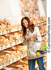 Grocery store: Young woman in bakery department holding...