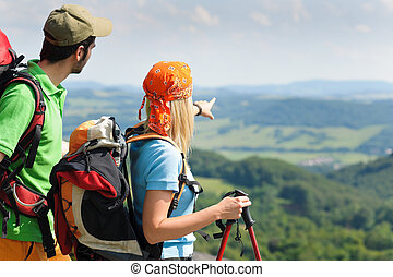 Hiking young couple point at panoramic view - Young backpack...