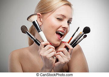 Young smiling woman with make up brushes on white