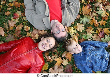 family lies on maple leaves