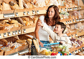 Grocery store shopping - Woman with child in a supermarket...