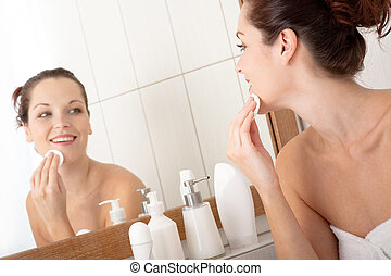 Body care series - Young woman cleaning her face in the...