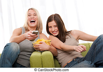 Students series - Two teenage girls having fun by television