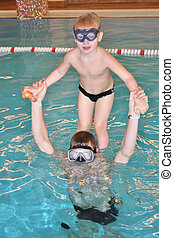 child with father in pool