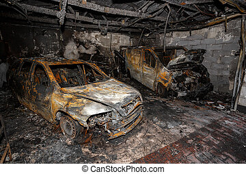 Close up photo of a burned out cars in garage after fire for...