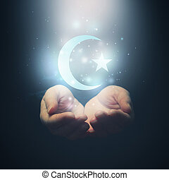 Female hands opening to light and Halh moon and star, symbol...