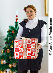 Happy pregnant woman holding a Christmas gift