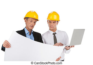 two professional builders looking at plan. businessmen...