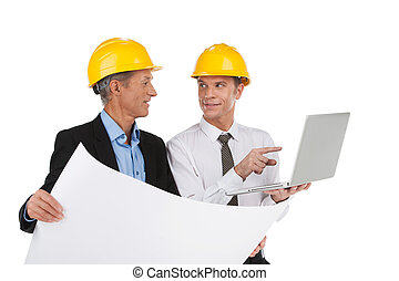 two professional designers drawing plan. foreman and engineer looking at plan and smiling