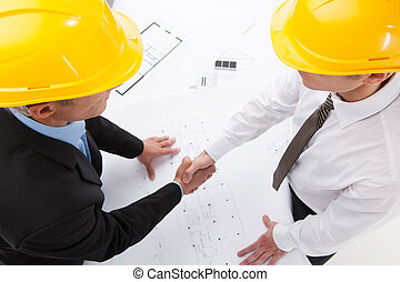 two architect shaking hands over plan. workers in helmets...