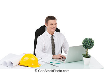 handsome male smiling and typing at computer. adult engineer...