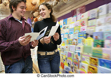 couple in postcards shop