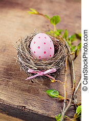 Easter egg in nest on wooden background.