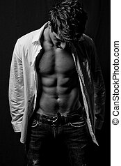 fitness male body - B&W young sporty man over black...