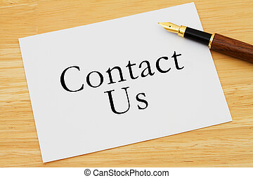 Contact Us - A white card with a fountain pen on a wooden...