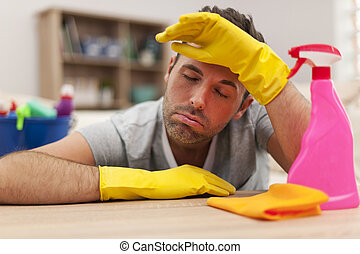 Tired man with cleaning equipment