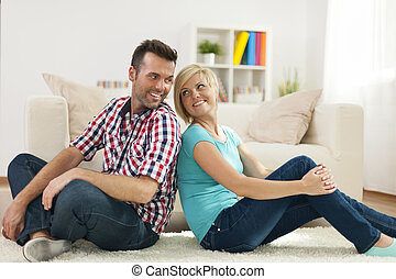 Loving couple sitting on carpet at home