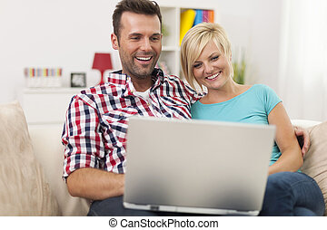 Excited couple looking on laptop at home