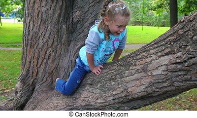 little girl climbs on tree