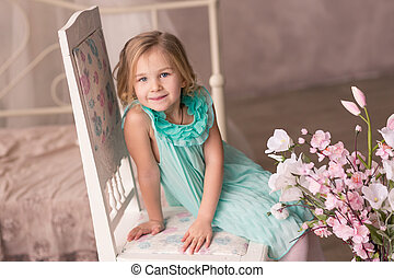 Beautiful little girl in fashion dress with spring flowers -...