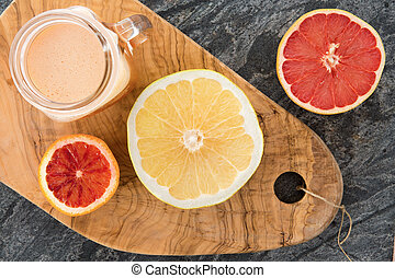 Freshly prepared grapefruit juice with halved ruby and...