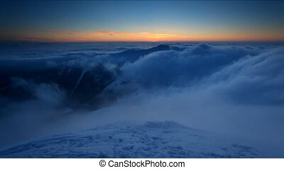 Winter mountain at sunset over clou