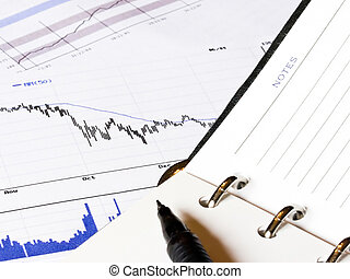 Falling finance graph and a notepad - Closeup of an opened...