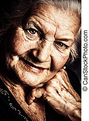 wise look - Portrait of a beautiful smiling senior woman.