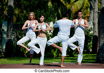 Yoga Class - A small group of adults attending a yoga class...